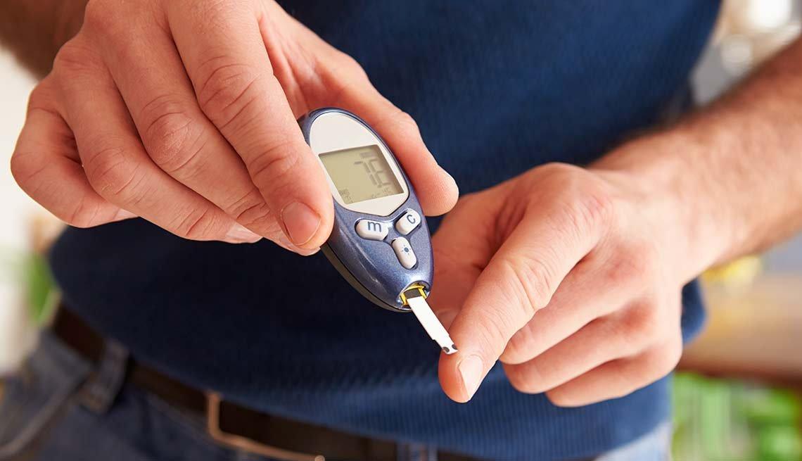 Hombre monitoreando su diabetes con un glucómetro