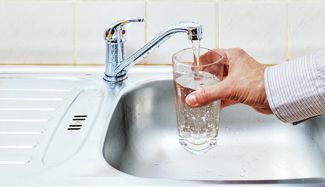 Hombre llenando un vaso de agua del grifo
