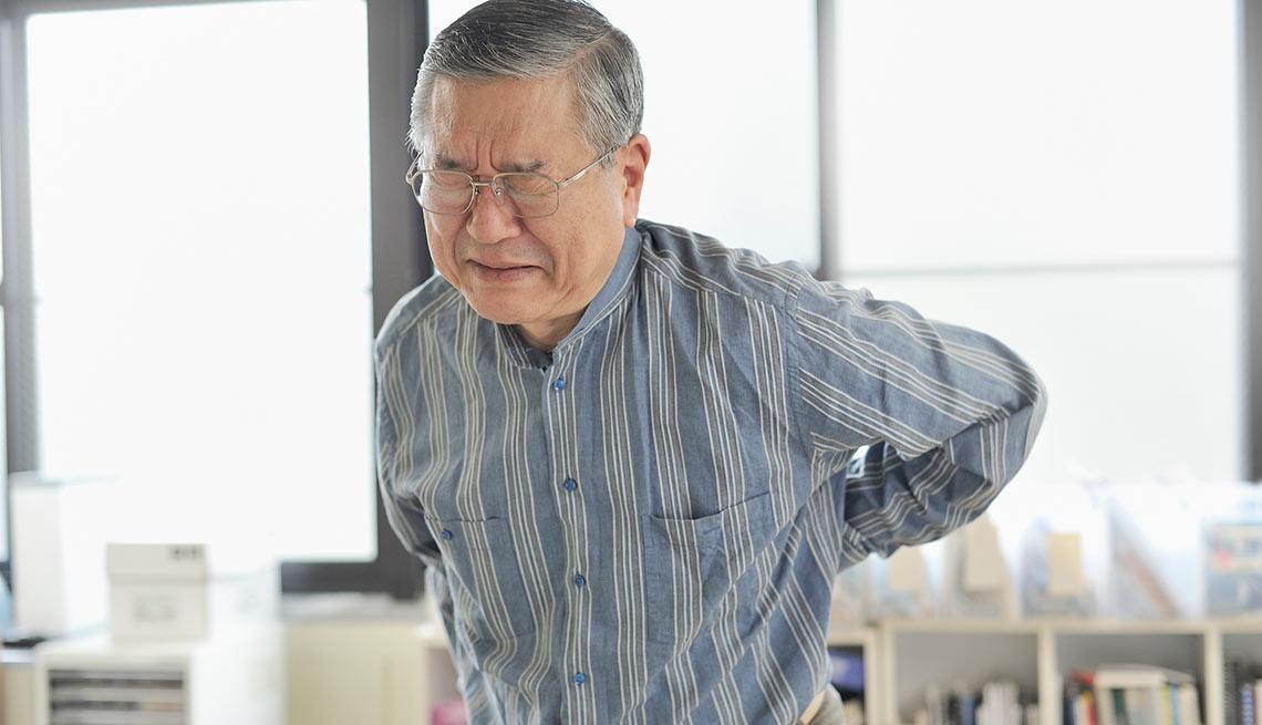 Hombre con las manos en su espalda en señal de dolor