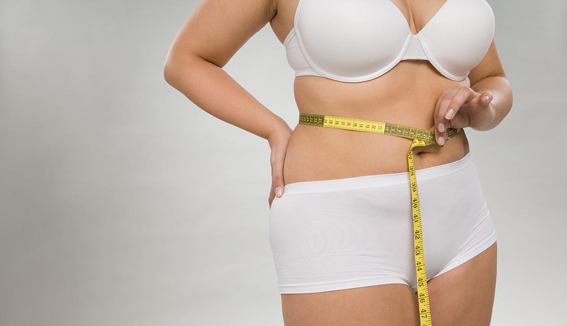 Mujer en ropa interior midiendo su cintura