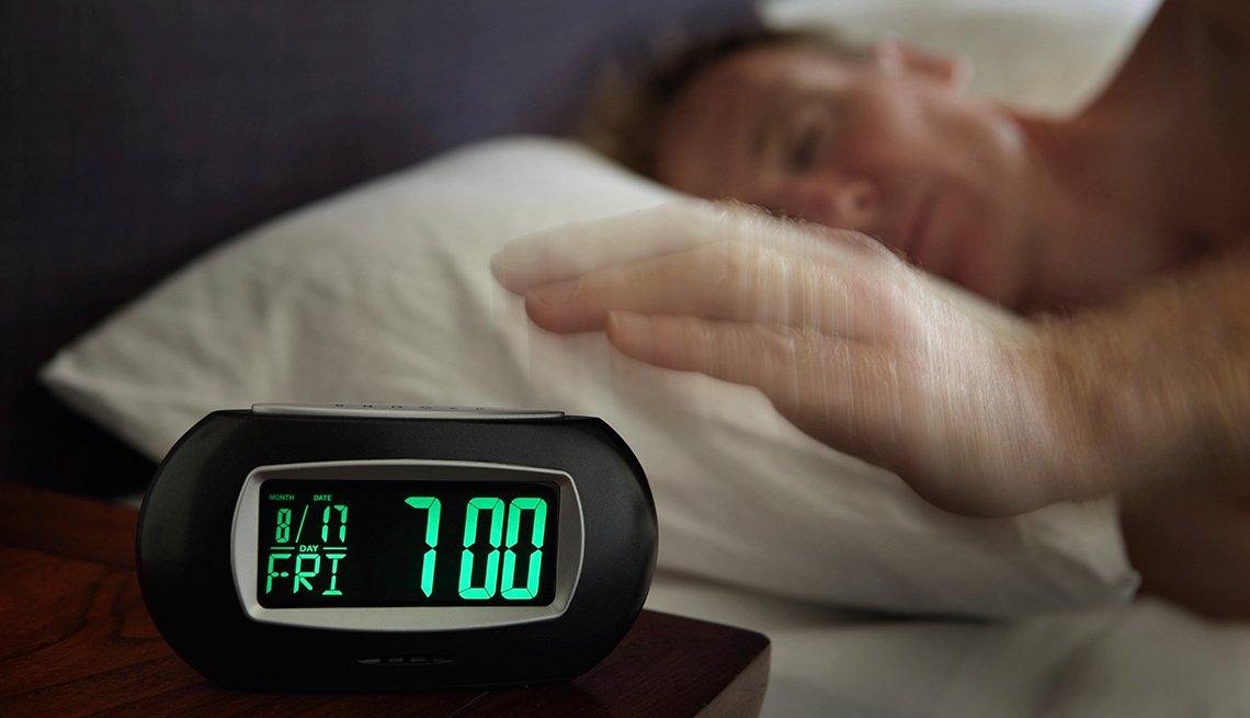 Hombre durmiendo y reloj el despertador