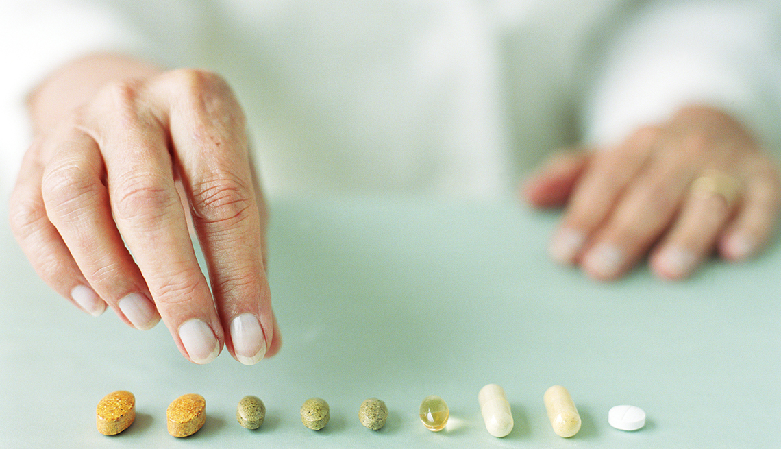 Mujer tomando varios medicamentos o vitaminas