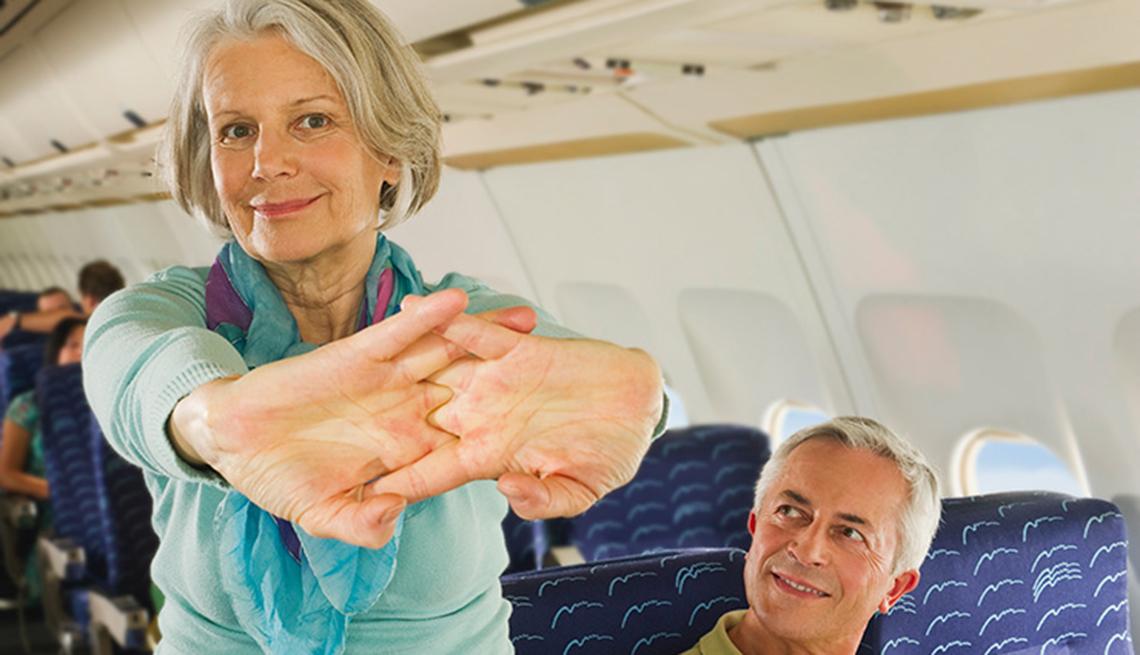 Mujer estirándose en la cabina de un avión