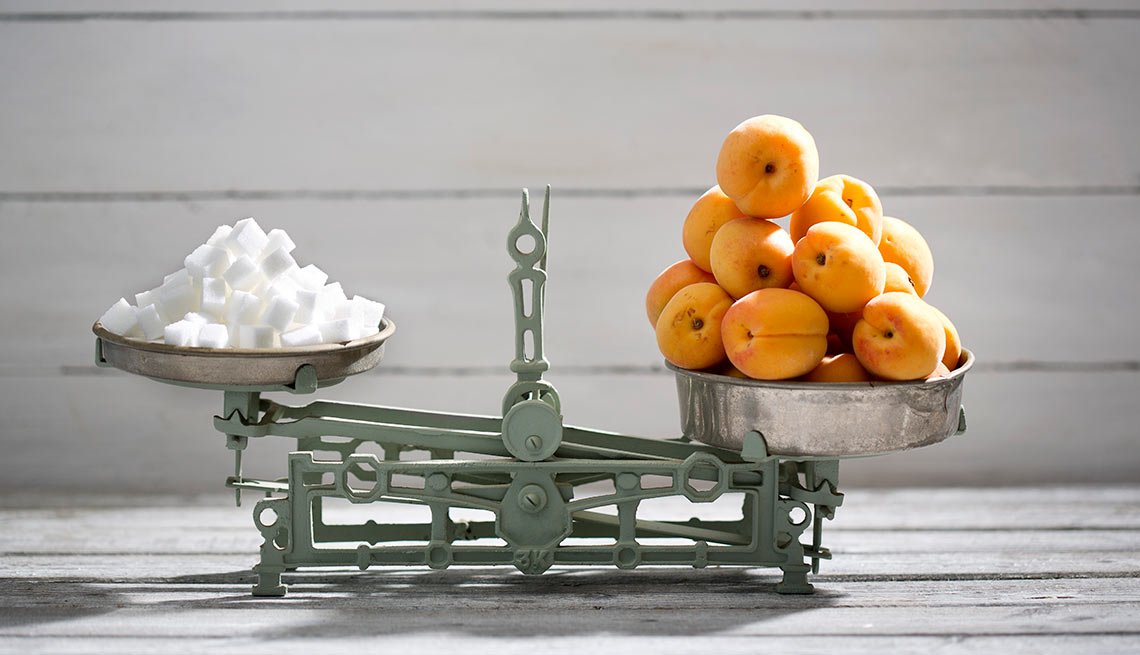 Balanza con cubos de azúcar a un lado y naranjas al otro