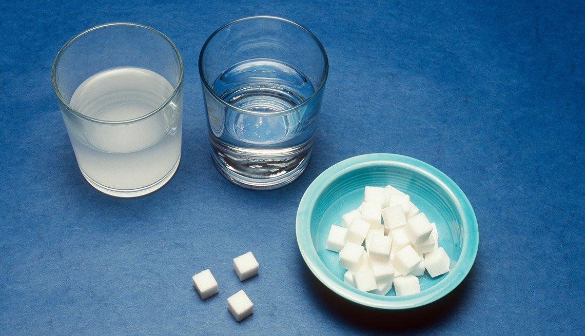Dos vasos con agua y un envase con terrones de azúcar