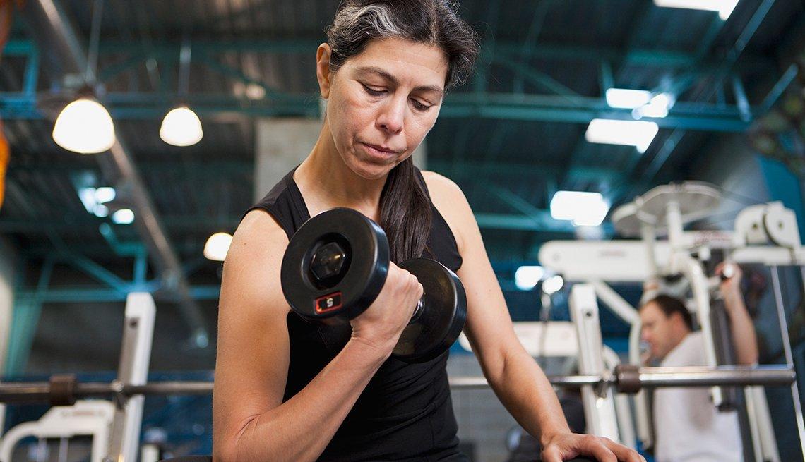 Mujer levantando pesas en un gimnasio