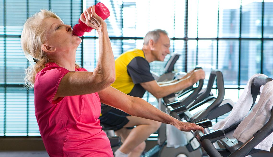 Mujer tomando agua mientras hace ejercicios en un gimnasio