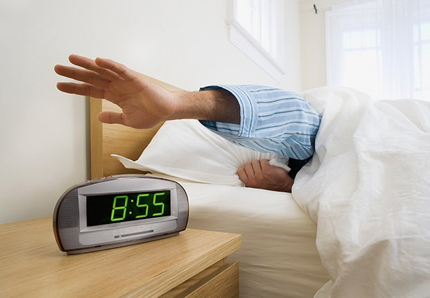 Hombre apagando su reloj despertador