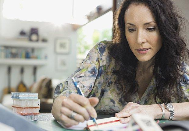 Mujer escribiendo en papel y bolígrafo