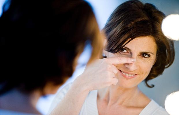 Mujer mirándose al espejo y examinando su nariz