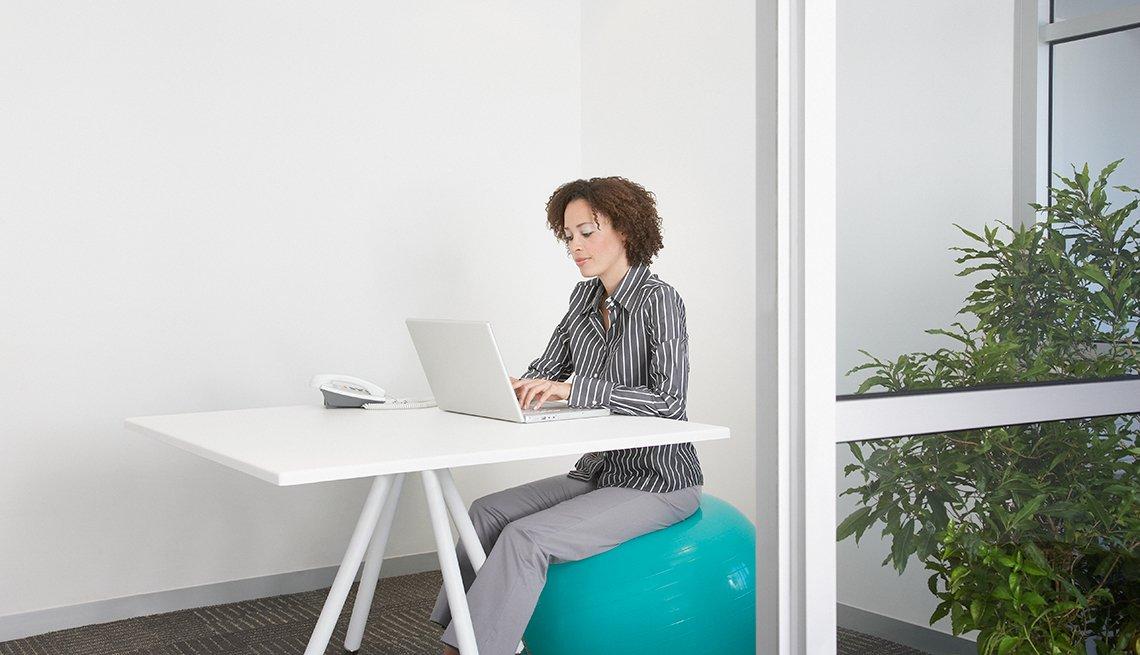 Mujer usando una computadora sentada en una bola de ejercicios