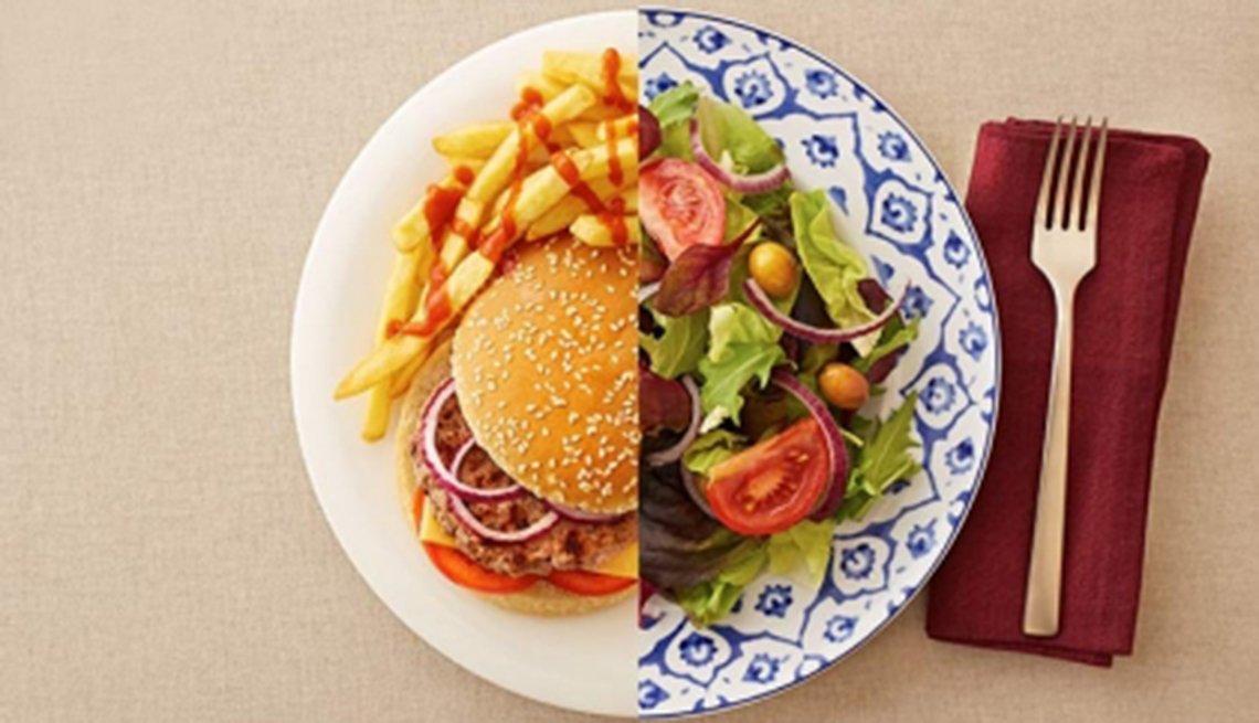 Mitad hamburguesa con papas fritas y la otra mitad ensalada