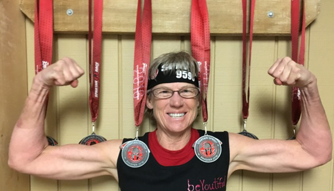 Lynn Asbury flexing in front of her medals