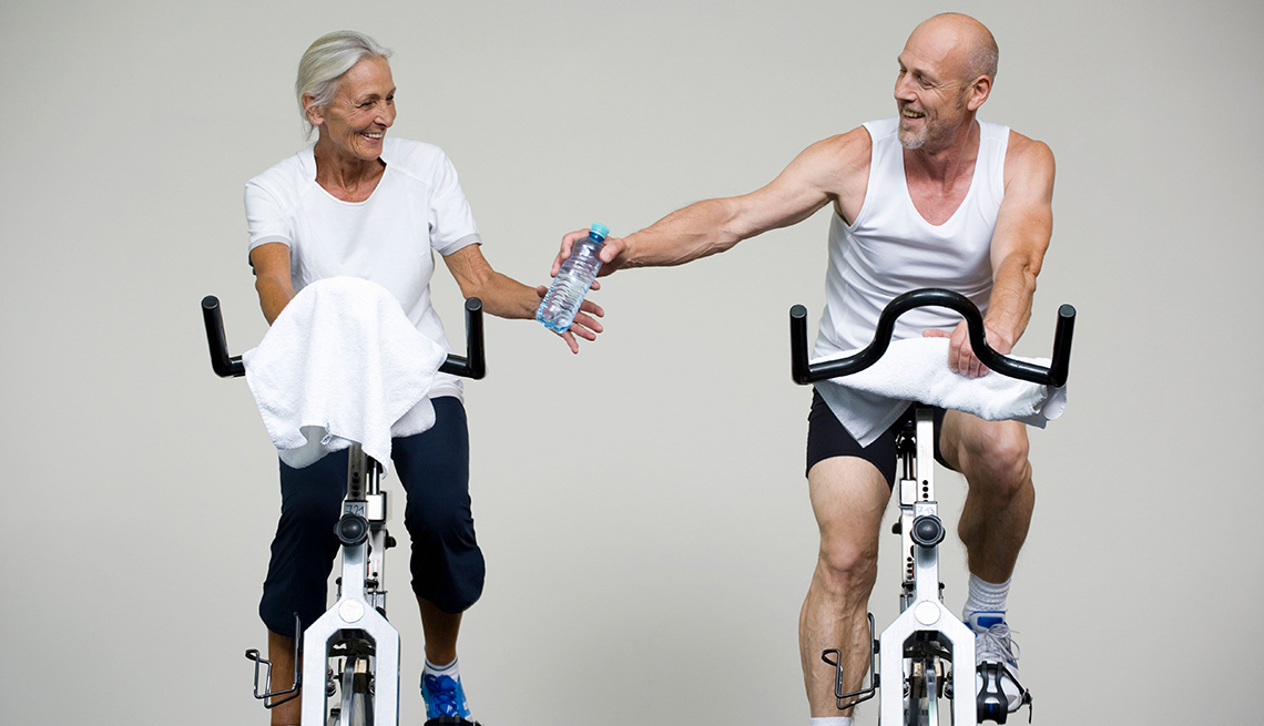 Couple on stationary bikes, passing a water bottle, Miniworkouts work