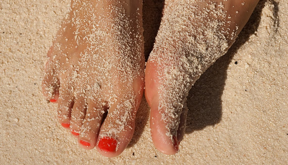 Feet with painted toenails in sand, Health Boosters