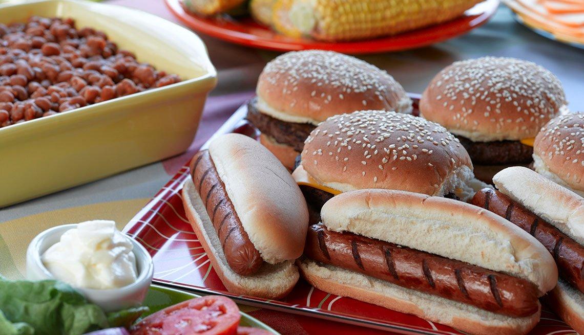Hot Dogs, habichuelas, ensalada y maíz sobre una mesa de picnic