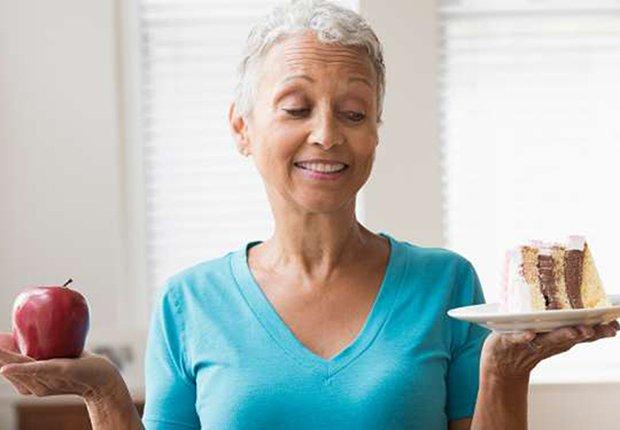 Mujer decidiendo entre una manzana y un pedazo de pastel