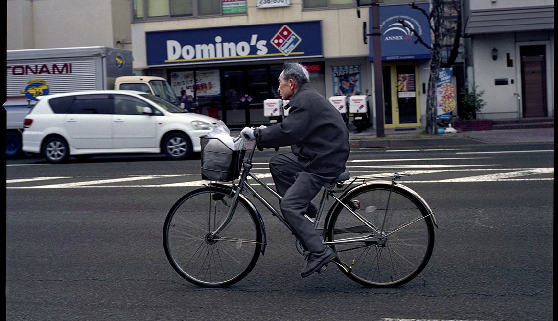 Man bicycling in city, Nagano, Japan, Longest Living place on Earth