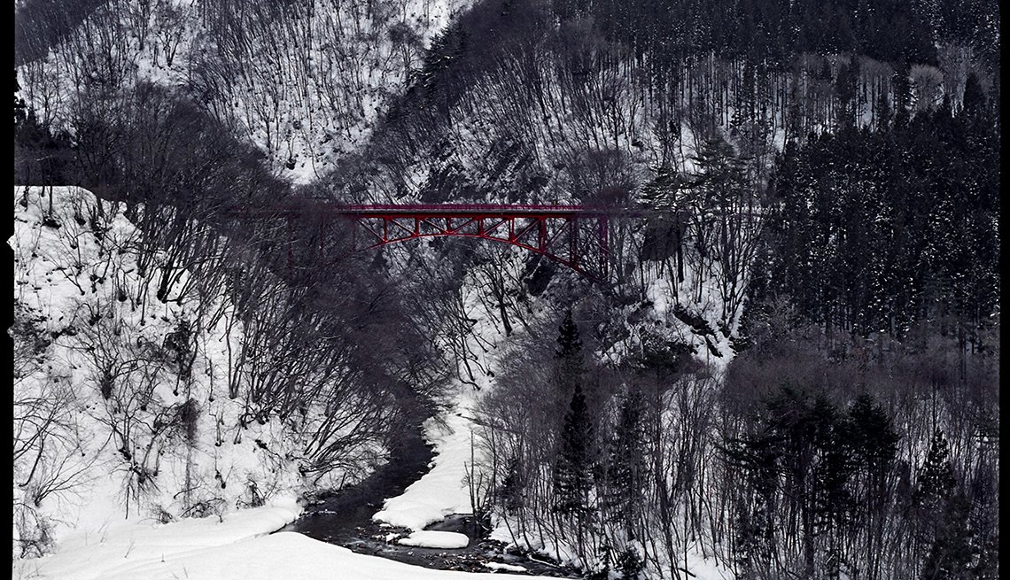 A red bridge in snowy tree covered hills, Yamada-Onsen, Japan, Longest Living place on Earth