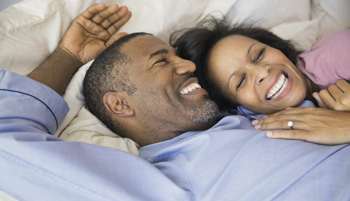 Couple laugh in bed, 7 Reasons to Have More Sex After 50