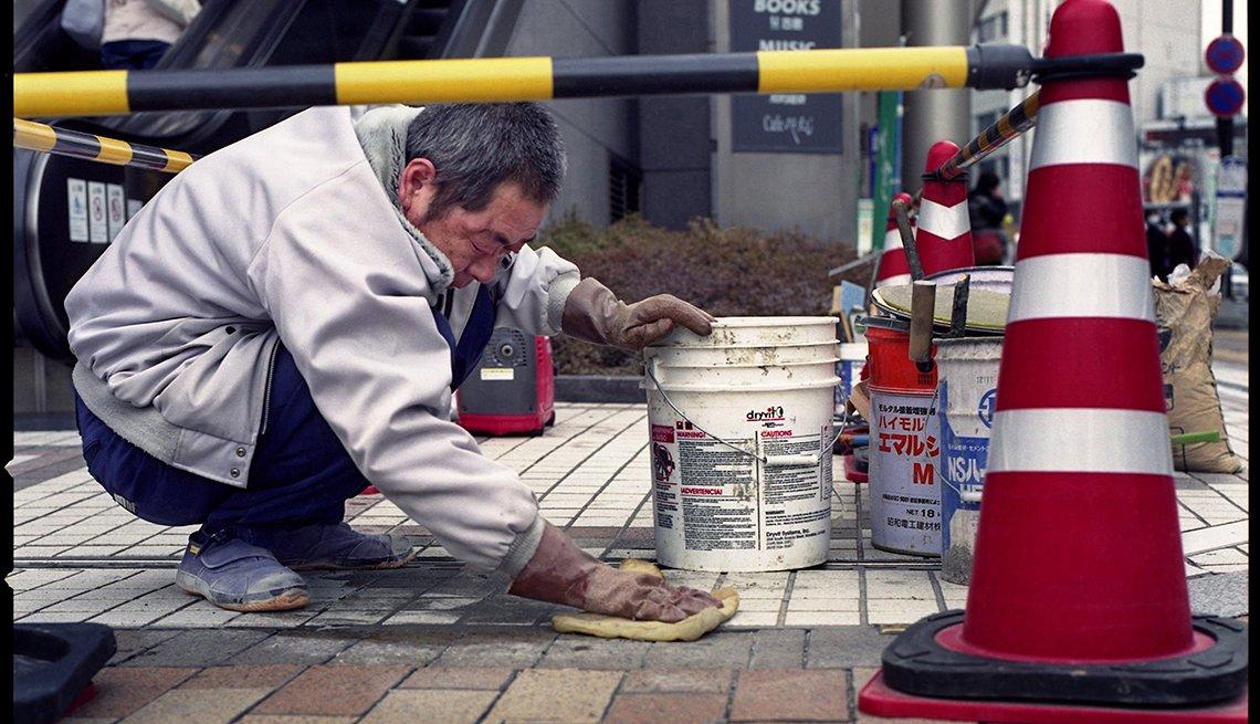 Older man working outdoors, paving sidewalk, Longest Living place on Earth