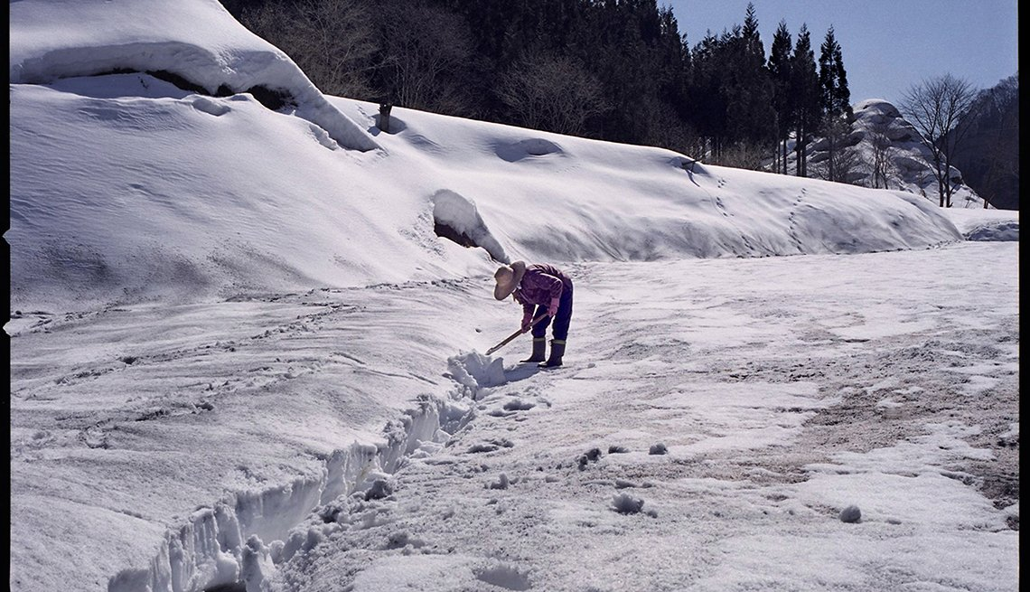Woman works in snow, sunny snow clearing, Longest Living place on Earth