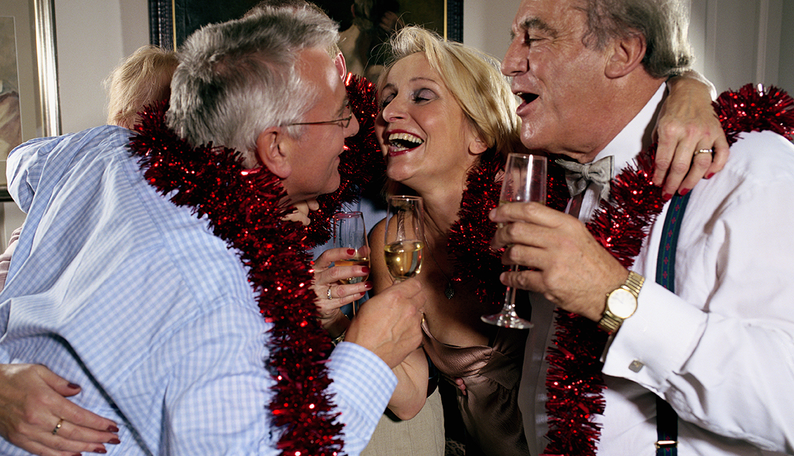 People celebrate at a holiday party, four people with wine and tinsel, singing, How Not to Gain Those 10 Holiday Pounds