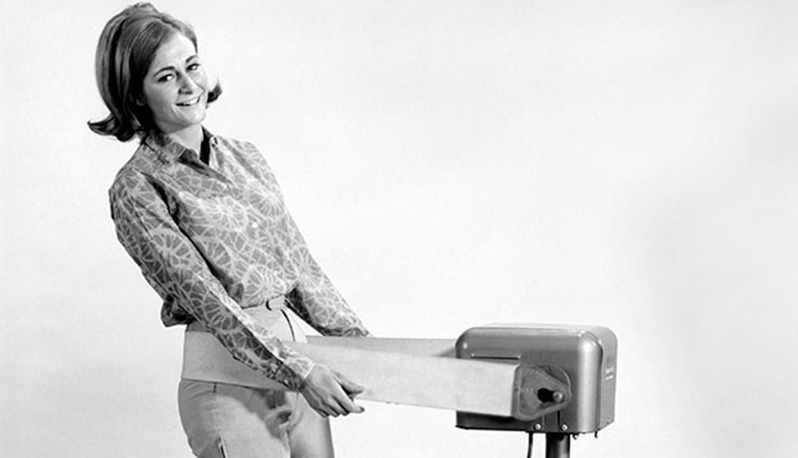1960s woman smiles at camera, Vibrating belt fitness machine, Boomer Fitness Fads