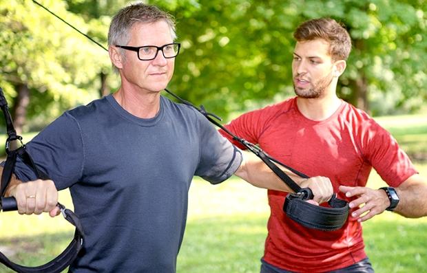 Hombre y su entrenador utilizando las bandas de TRX