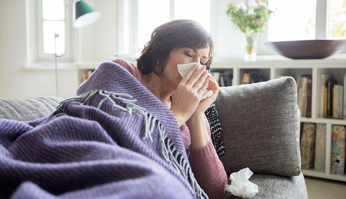 Mujer con gripe acostada en un sofá