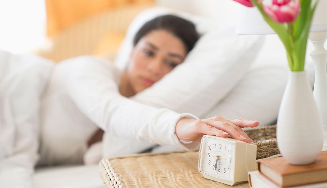 Mujer en su cama apaganlo la alarma
