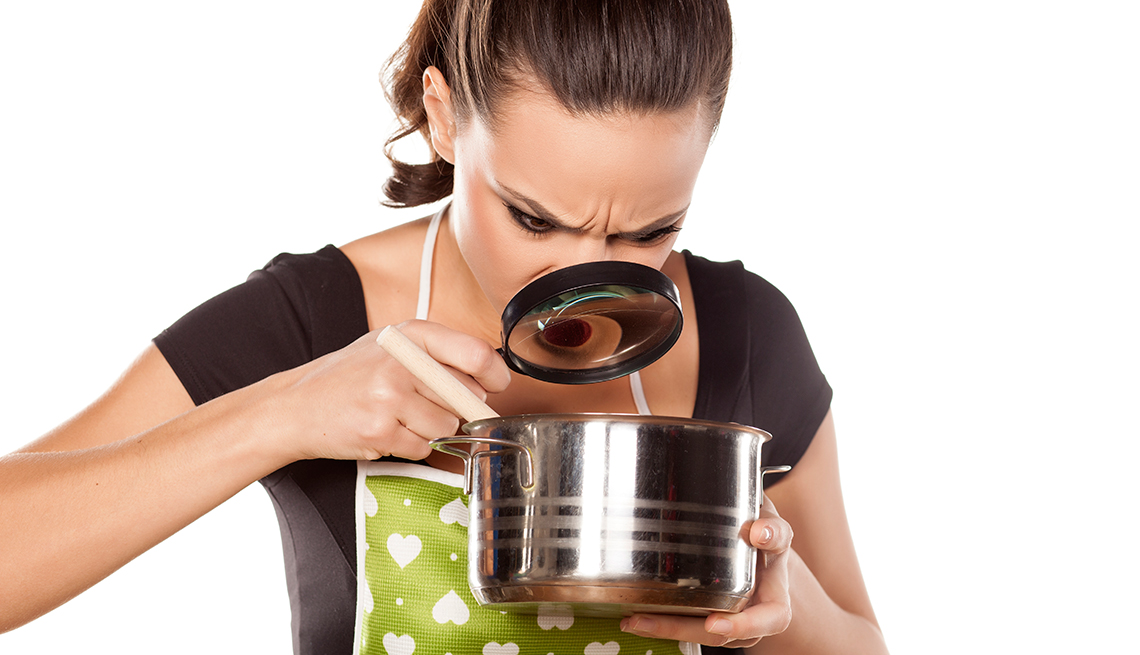 Mujer con una lupa mirando el contenido de una olla