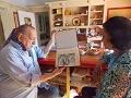 Dos adultos en un hogar viendo un album de fotografías