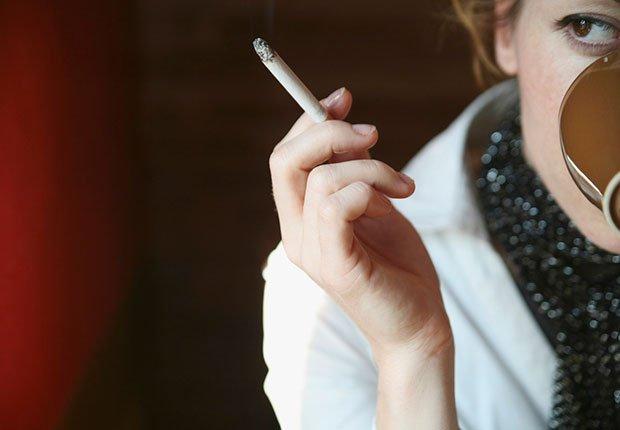 Mujer fumando y tomando café