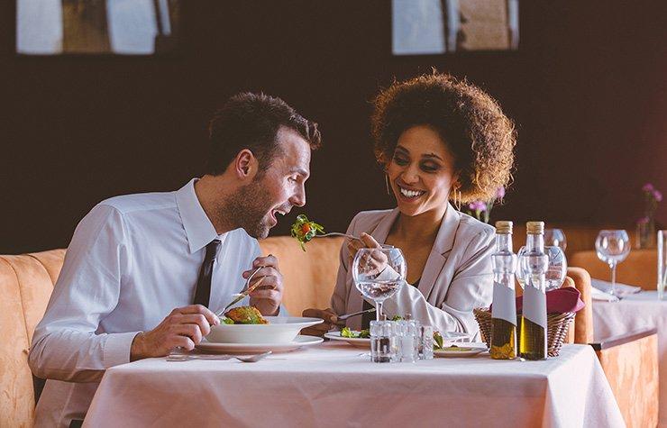 Alimentos que debes evitar antes de una salida romántica - Una pareja se da mutuamente comida