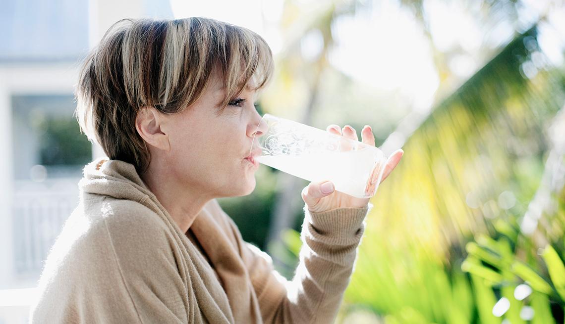 Mujer tomándose un vaso de jugo