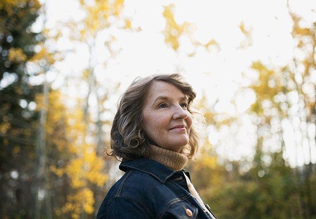 Mujer mayor en un bosque. Aprende cómo mejorar la apariencia de tu cuello.