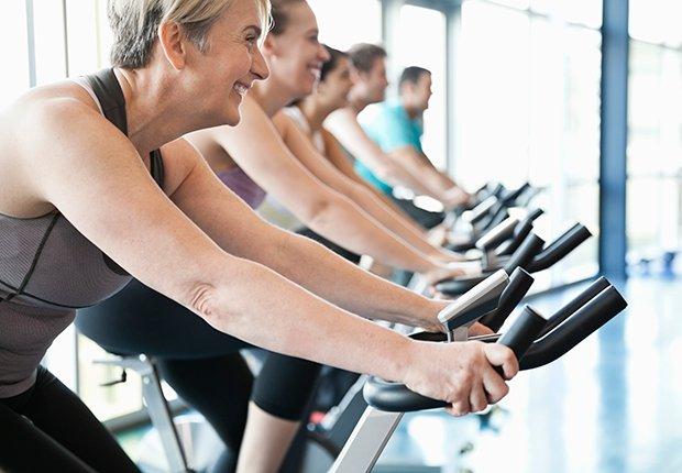 Mujeres en una clase de spinning como ejercicio para prevenir la caída del cuello.