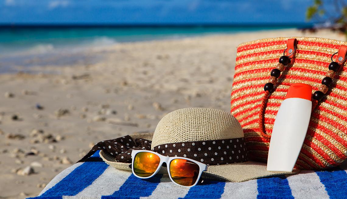 item 1 of Gallery image - Sombrero, gafas y cartera en una toalla en la playa