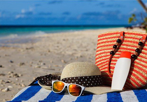 Sombrero, gafas y cartera en una toalla en la playa