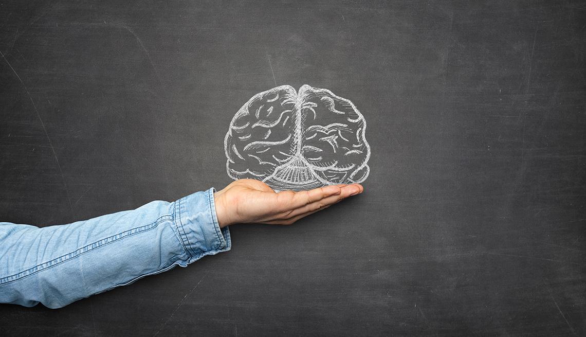 Mano simulando que sostiene un cerebro dibujado en un pizarrón
