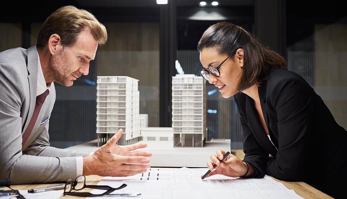 Hombre y mujer dialogando en un trabajo