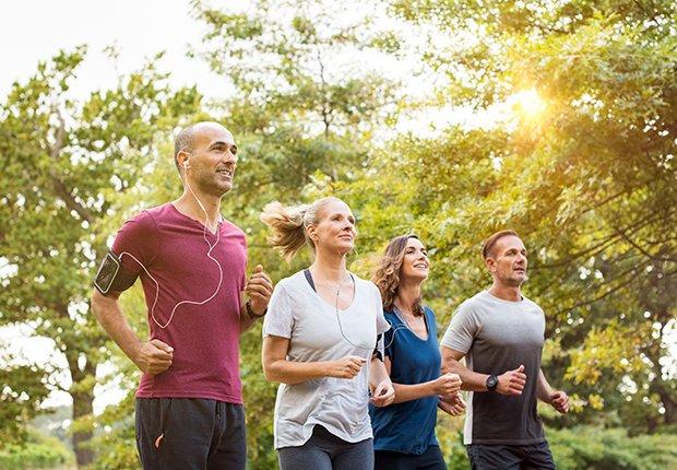 Cuatro adultos corriendo al aire libre