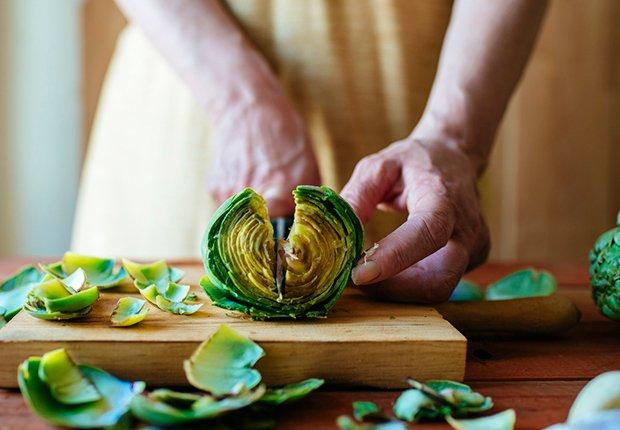 Mujer cortando una alcachofa