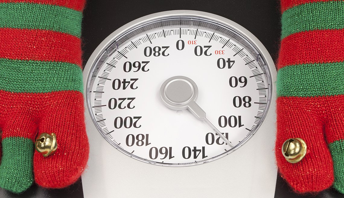 Persona en una balanza utilizando medias con motivos navideños