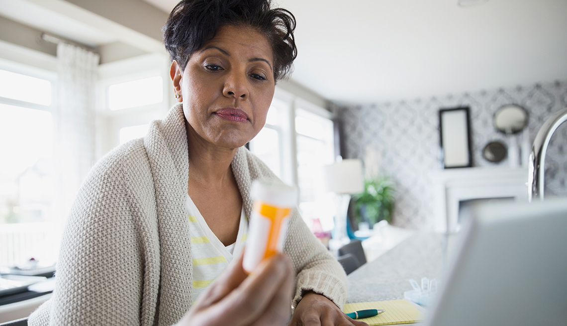 Mujer examinando un frasco de medicamentos