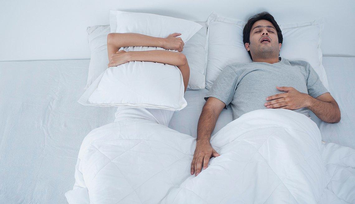 Pareja acostada en la cama, hombre dormido roncando y mujer cubriéndose con una almohada