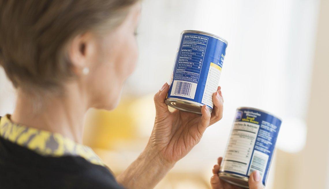 Mujer leyendo la etiqueta de una lata de comida