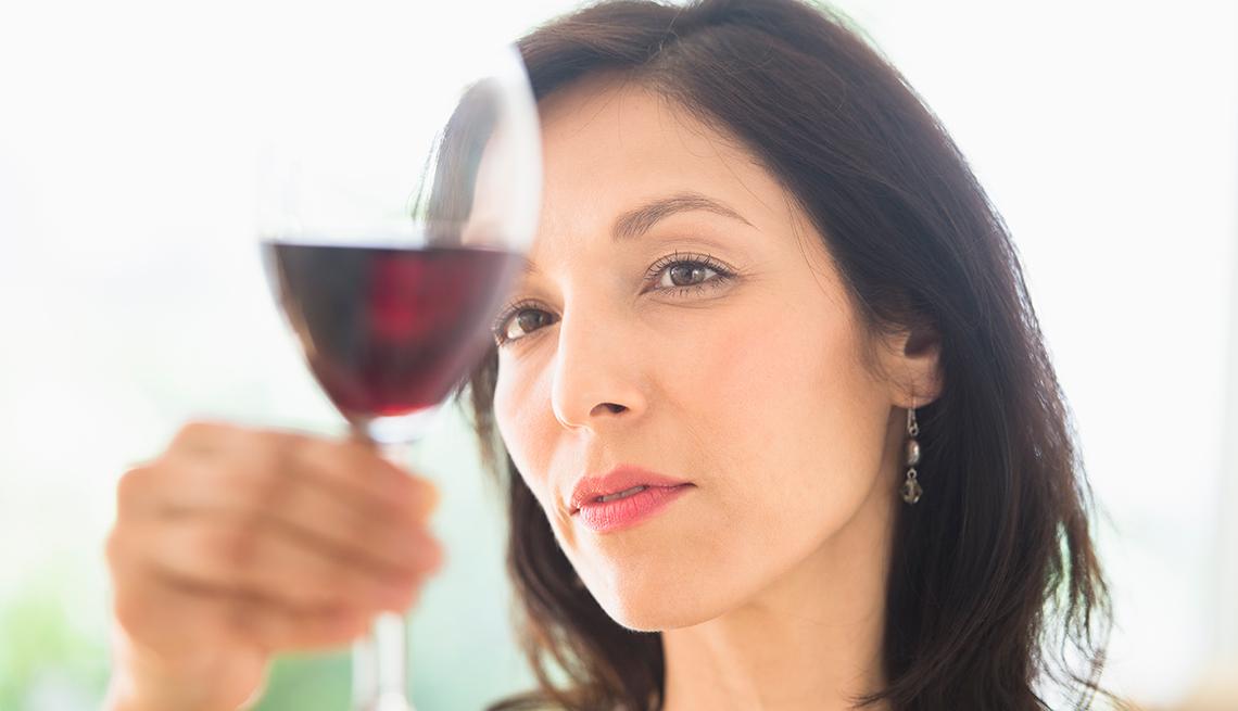 Mujer mirando su copa de vino