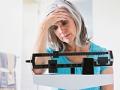 Mujer pesándose y preocupada por su peso